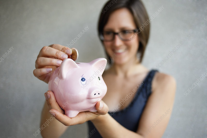 Woman putting coin into piggybank