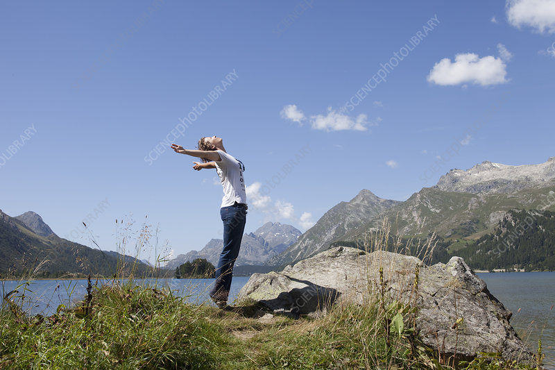Woman standing on lake with open arms