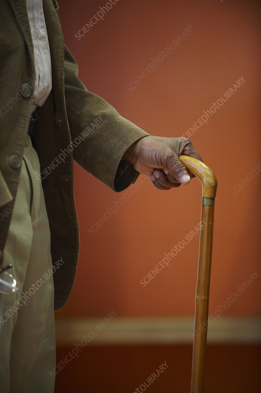 Elderly man's hand on walking stick
