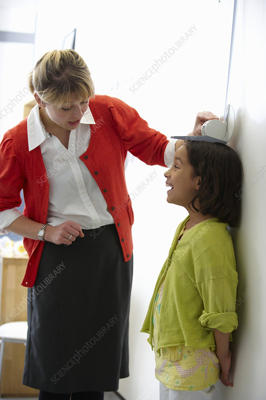 Doctor measuring height of young girl
