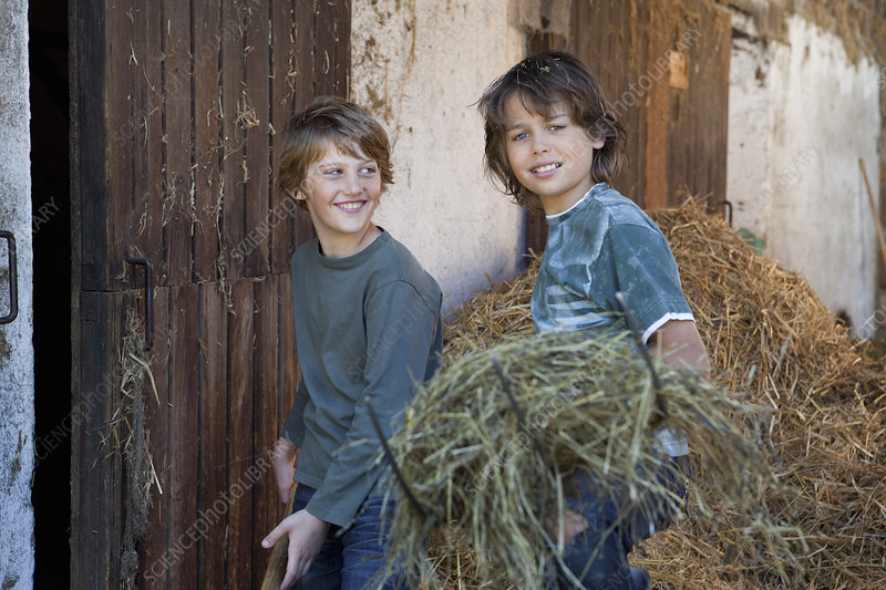 Two boys with hayforks, happy