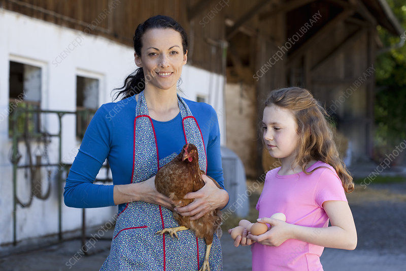 Farmwoman with hen, daughter with eggs