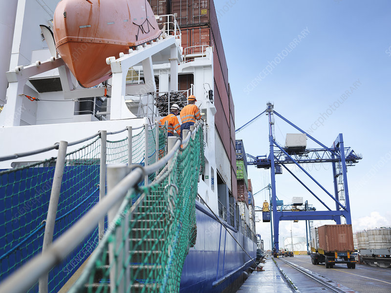 Sailors watching container ship loading