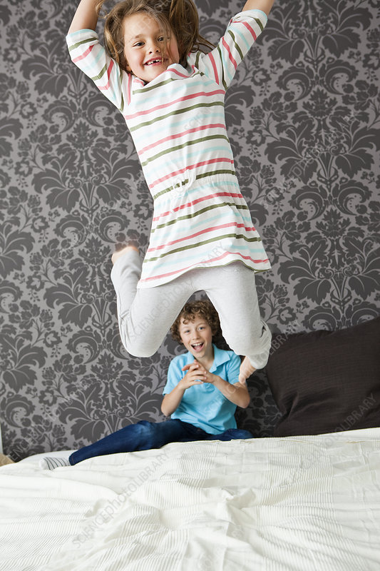 Girl jumping in bed