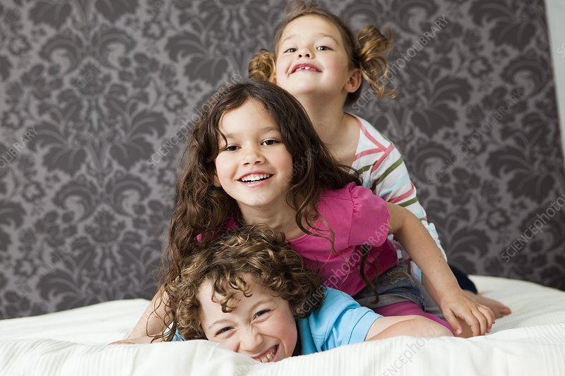 Three kids lying top of each other