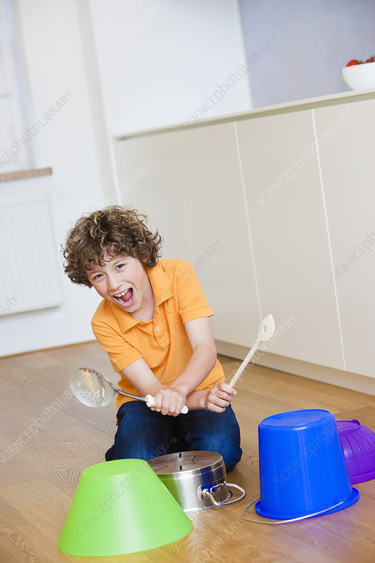 Boy playing drums on kitchen stuff