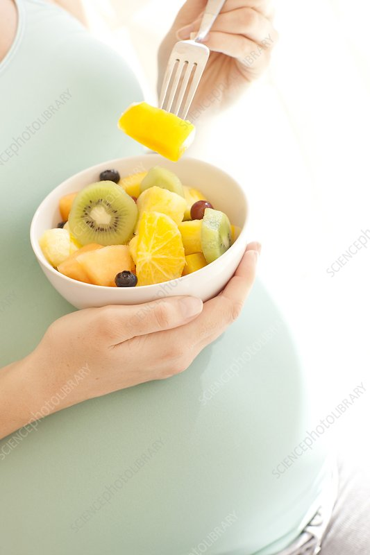 Pregnant woman eating a fruit salad