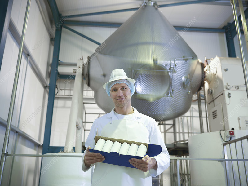Worker holding goat's butter in dairy