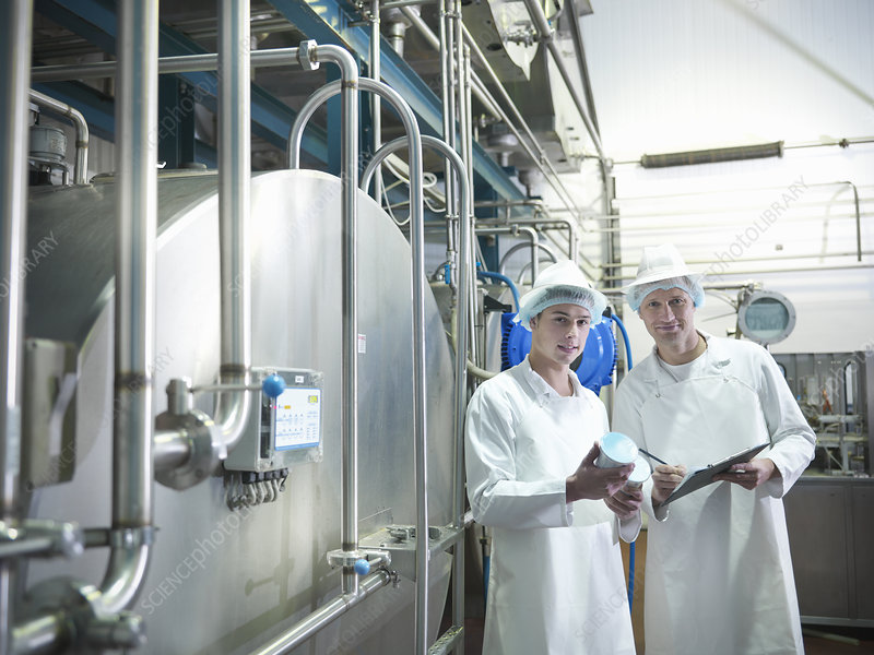 Workers inspecting goat yogurt in dairy
