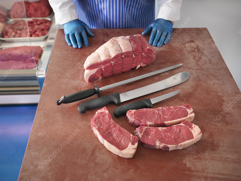 Butcher with knives and cuts of pork