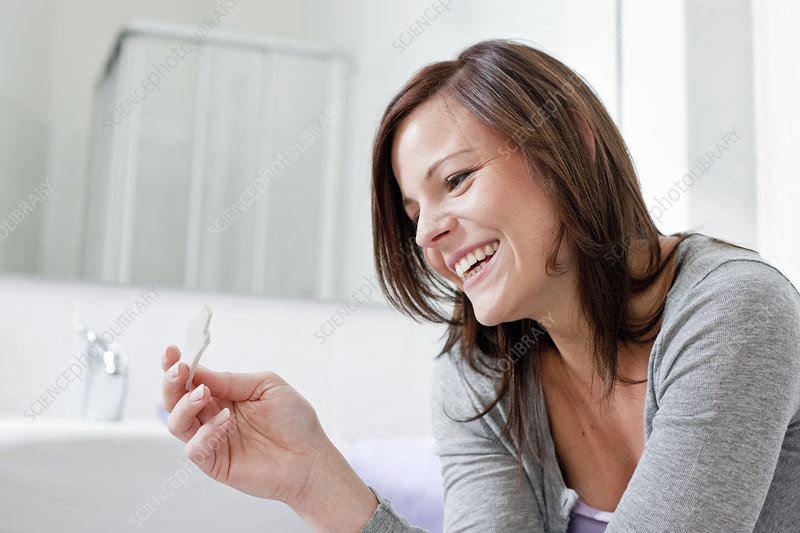 Smiling woman taking pregnancy test