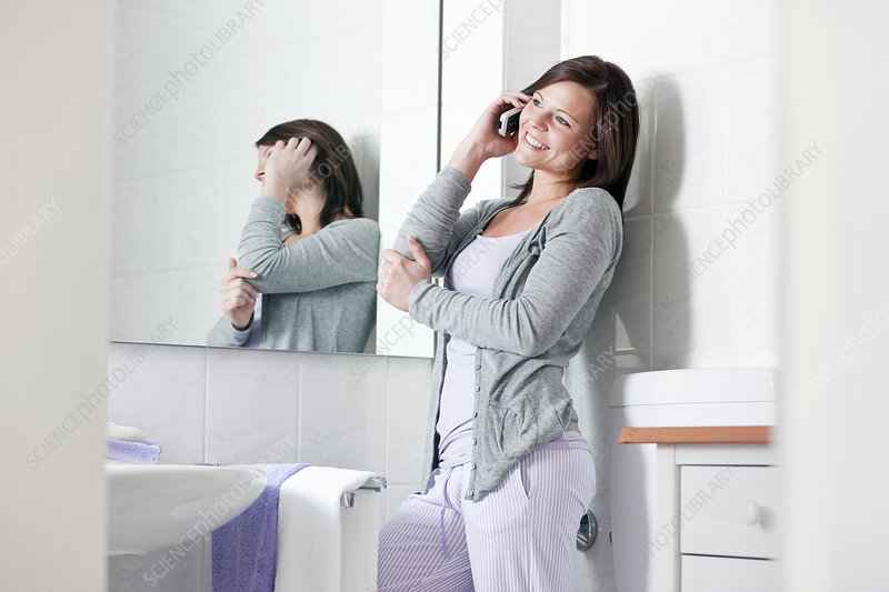 Woman talking on cell phone in bathroom