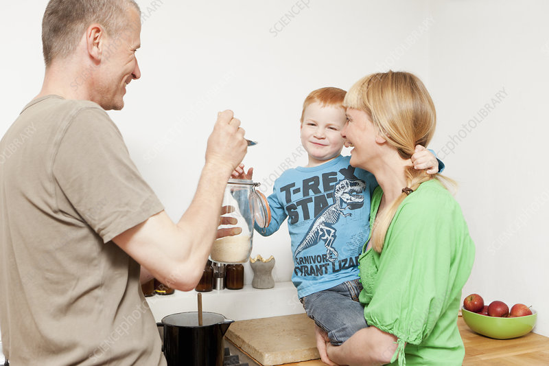 Parents feeding reluctant son in kitchen