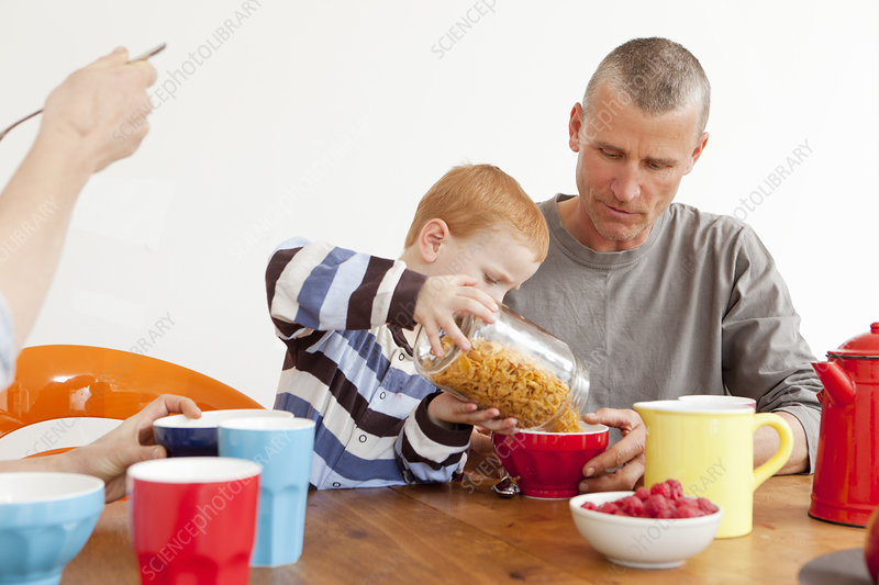 Boy pouring father bowl of cereal