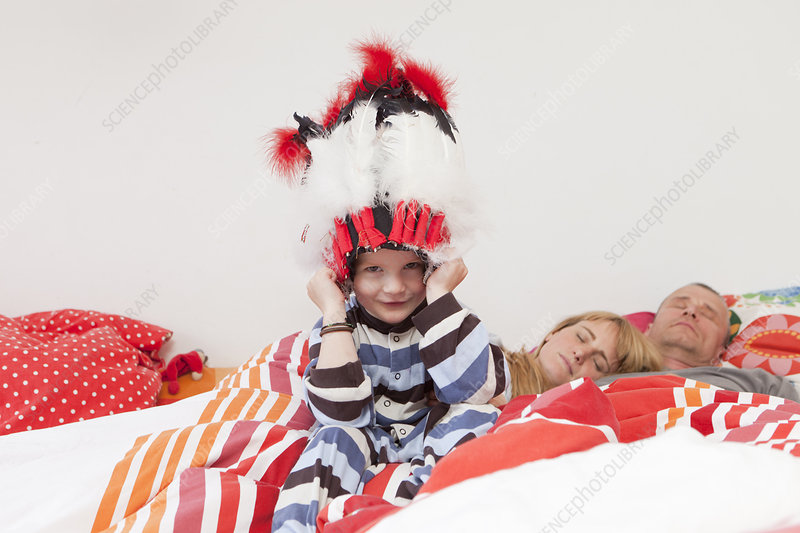 Boy wearing war bonnet in parents' bed
