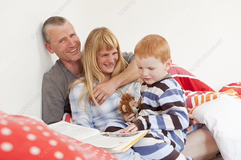 Family reading in bed together