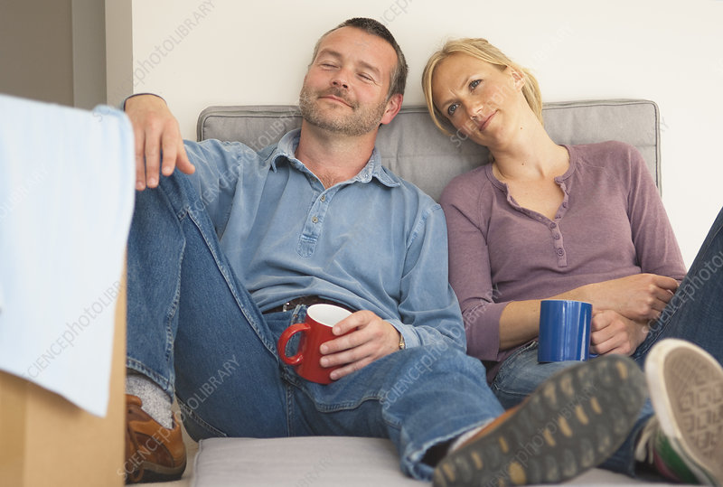 Couple having coffee on sofa together