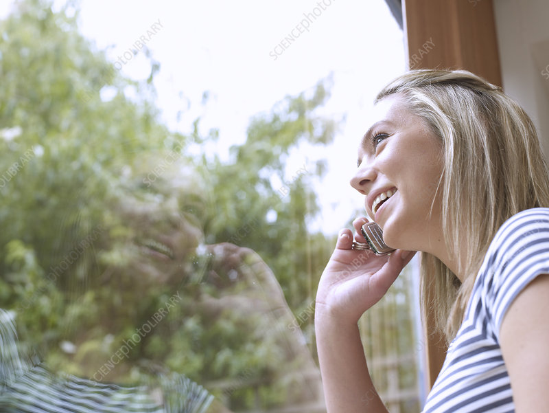 Woman talking on cell phone at window