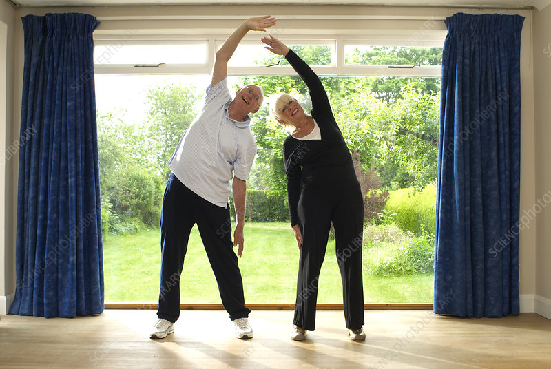 Couple stretching together indoors