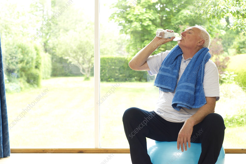 Older man drinking water during exercise