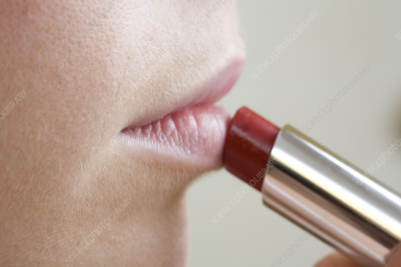 Close up of woman applying lipstick