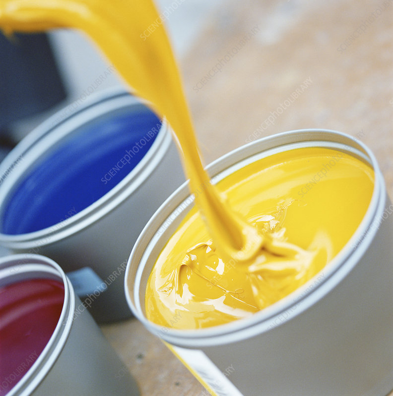 Yellow paint pouring into bucket