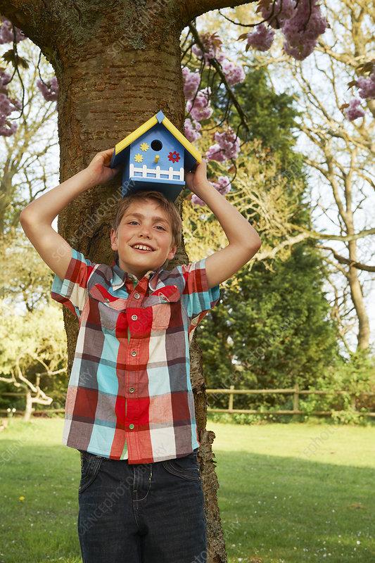 Boy holding birdhouse on his head
