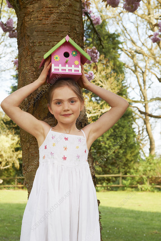 Girl holding birdhouse on her head
