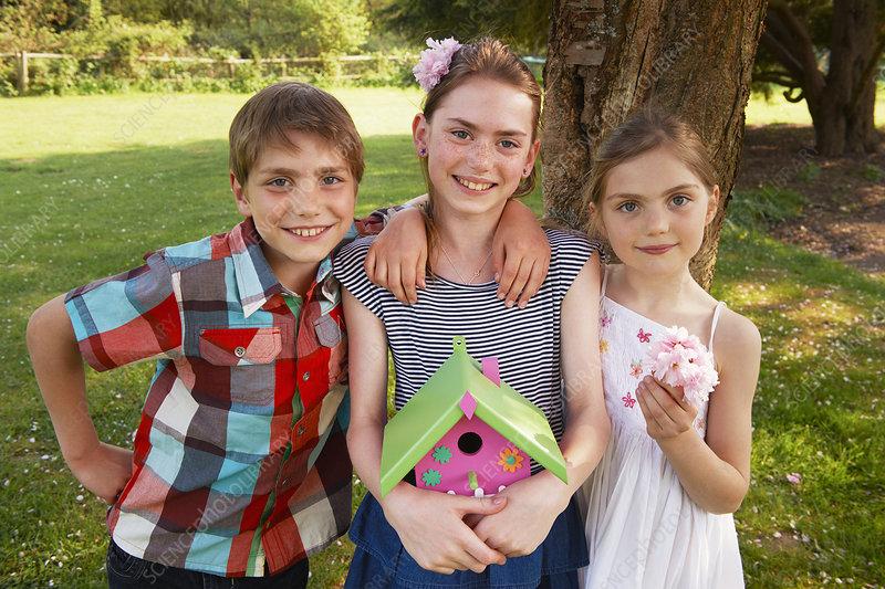 Children holding birdhouse in backyard