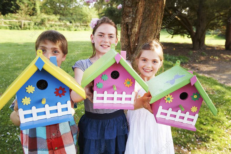 Children holding birdhouses in backyard