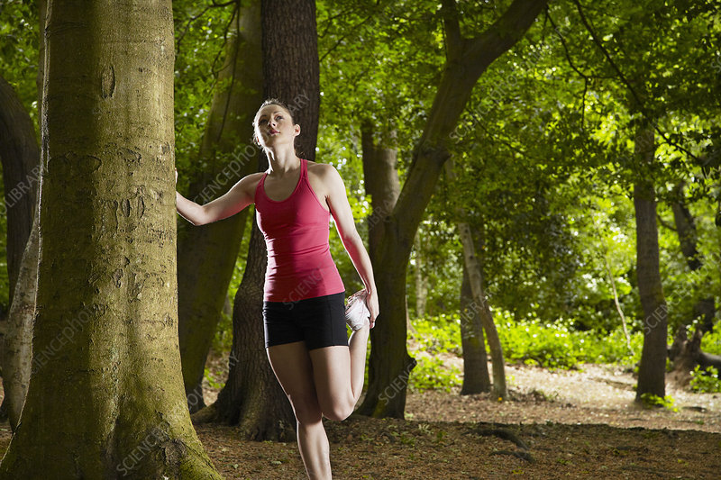 Jogger stretching in forest