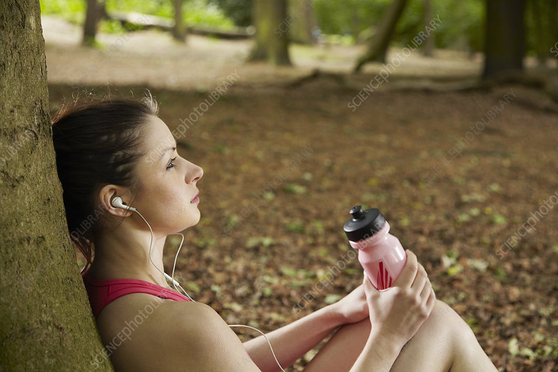 Jogger listening to mp3 player in forest