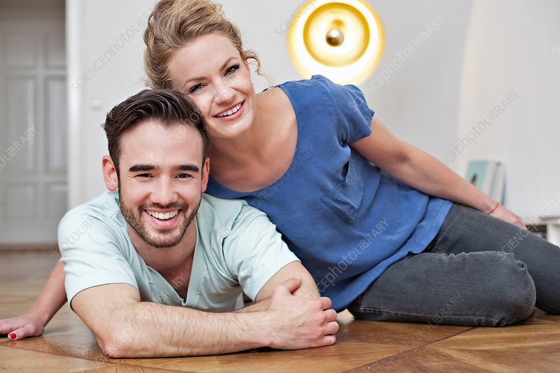 Smiling couple embracing on floor