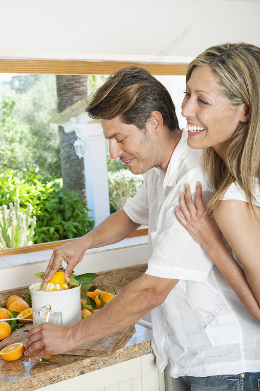 Couple using a juicer in kitchen