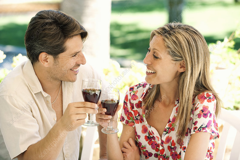 Couple toasting each other outdoors