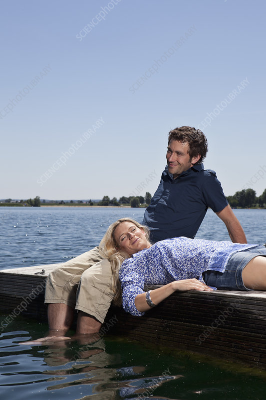 Couple relaxing together on dock