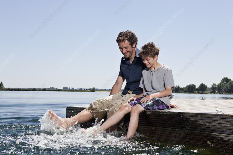 Father and son relaxing together on dock