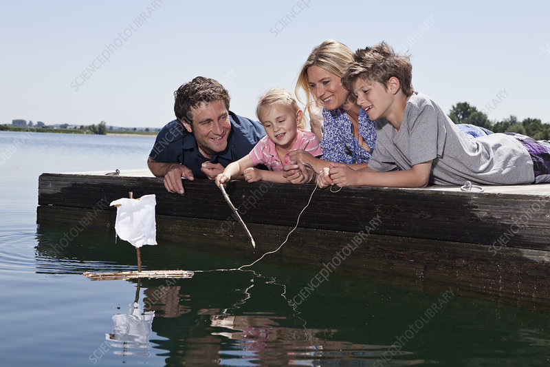 Couple playing with toy boat on dock