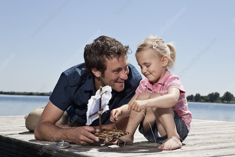Father and daughter playing on dock