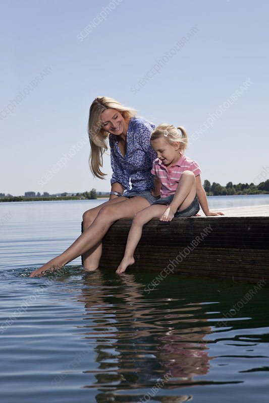Mother and daughter relaxing on dock