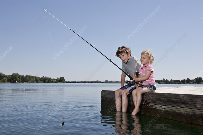 Brother and sister fishing on dock