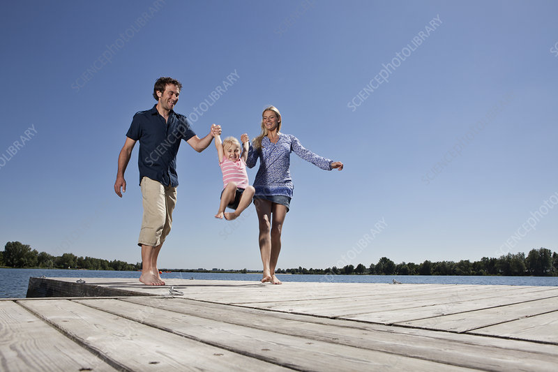 Parents swinging daughter on dock