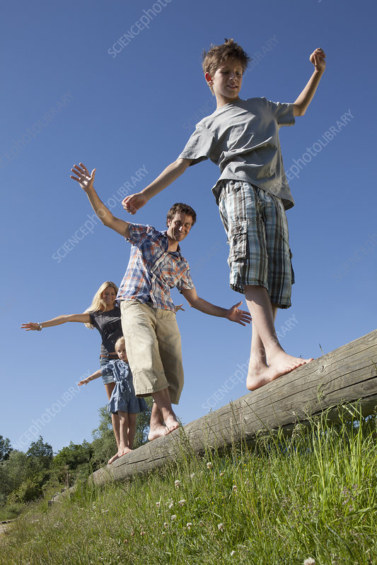 Family balancing on log outdoors