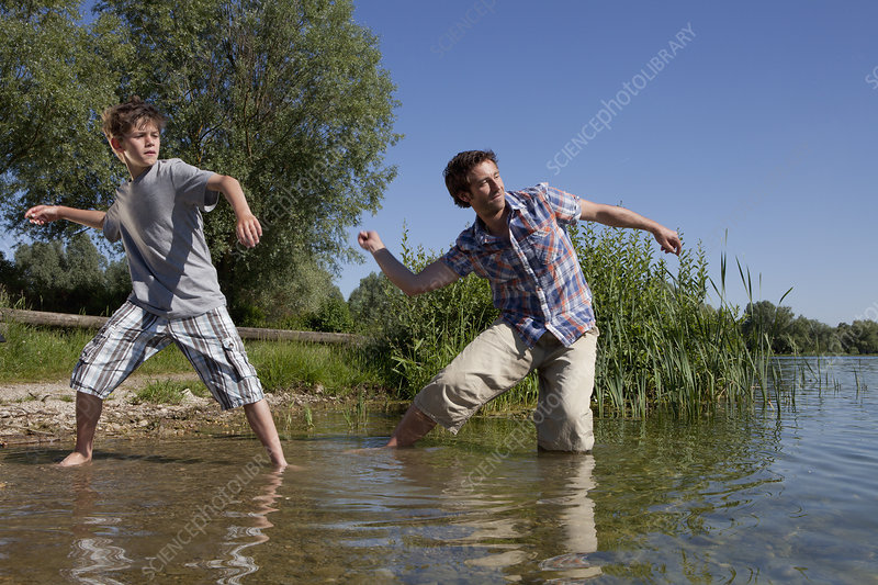 Father and son skipping rocks on lake
