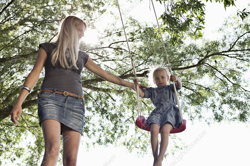 Mother pushing daughter on swing