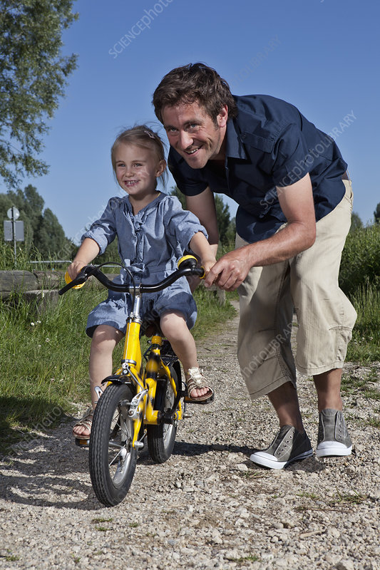 Father helping daughter ride bike
