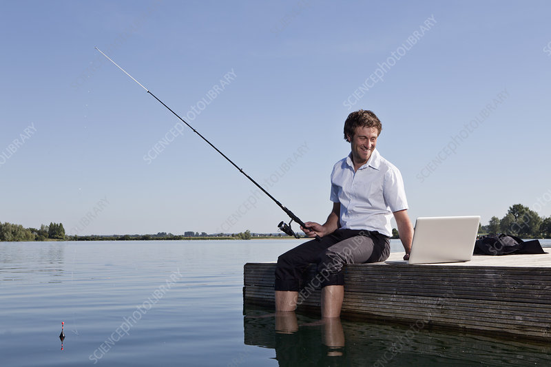 Man fishing and using laptop on dock