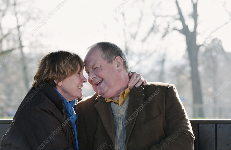 Older couple touching foreheads outdoors
