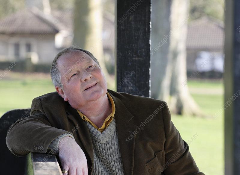 Older man sitting on park bench