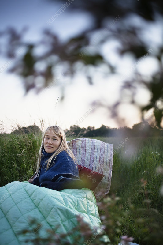 Woman wrapped in blankets outdoors